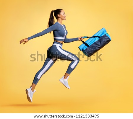 Go to training. Sporty woman with bag running in silhouette on yellow background. Dynamic movement. Side view. Sports and healthy lifestyle #1121333495