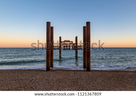 The ruins of West Pier in Brighton with a sunset sky behind #1121367809