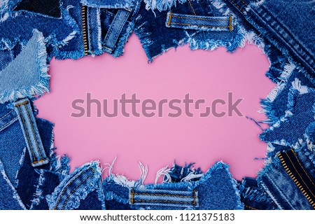 Denim frame from Lots of little ripped pieces of denim jeans fabric on pink leather background. Ripped Destroyed Torn Denim Frame, copy space #1121375183