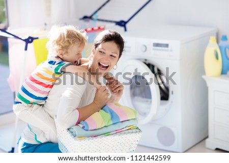 Mother and kids in laundry room with washing machine or tumble dryer. Family chores. Modern household devices and washing detergent in white sunny home. Clean washed clothes on drying rack.  #1121442599