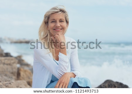 Smiling friendly woman relaxing on rocks at the beach on a misty day sitting with her chin resting on her hand looking at camera #1121493713