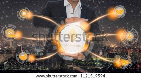 Ethereum and cryptocurrency investing concept - Businessman holding Ethereum (ETH) with mobile application business icons showing exchanging, trading, transfer and investment of blockchain technology. #1121519594