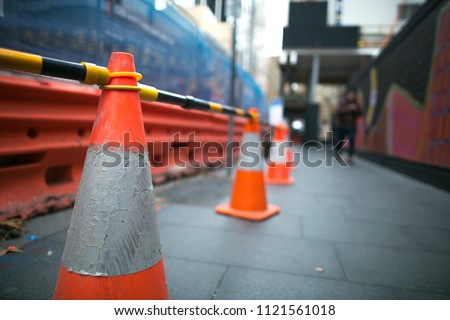 Red and white witches hat cone traffic warning sign  barrier applying on busy street downtown on pedestrian footpath, road under construction in Sydney city CBD,  Australia