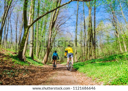 couple riding bicycle in forest in warm day #1121686646