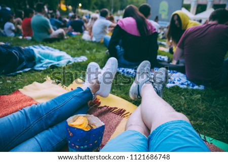 people watching movie in open air cinema in city park Royalty-Free Stock Photo #1121686748