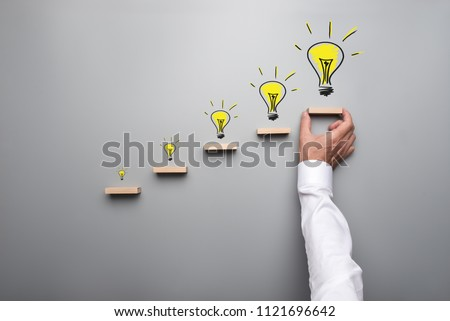 Five hand drawn light bulbs representing a new idea on wooden steps with male hand holding or placing the last step. Conceptual image of business vision. #1121696642