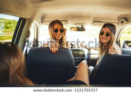 Three women enjoying road trip. They chatting while sitting in the car. #1121705357