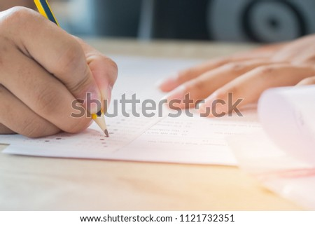 Education test concept : Man Hands high school, university student holding pencil for testing exams writing answer sheet and exercise for taking in exam paper on wood table at classroom with uniform #1121732351