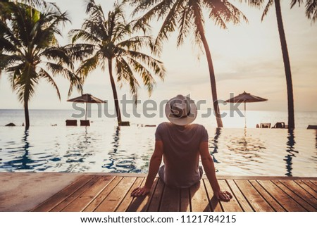 tourist in luxury beach hotel near luxurious swimming pool at sunset, getaway, tropical exotic holidays vacation, tourism and travel #1121784215