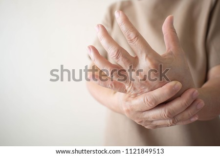 Elderly woman suffering from pain, numbness or weakness in hands. Causes of hurt include osteoarthritis, rheumatoid arthritis, gout, peripheral neuropathy, lupus or Raynaud's phenomenon. Health care.