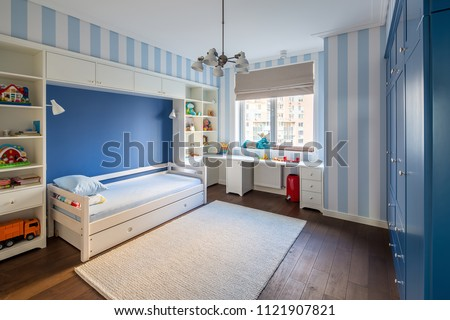 Modern kid's room with striped blue-white walls and a parquet with a carpet on the floor. There is a white bed with pillows, lockers and shelves with toys and books, table, blue wardrobe, window, bin. #1121907821