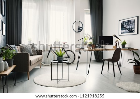 Bright living room interior with sofa with cushions, bike under the window with curtains and hairpin desk with lamp and computer for remote work #1121918255