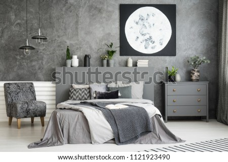 Moon art decor on the wall in a stylish grey bedroom interior with a big bed in the middle and an armchair and drawer cabinet besides. Cushions and covers on the bed. Real photo. #1121923490