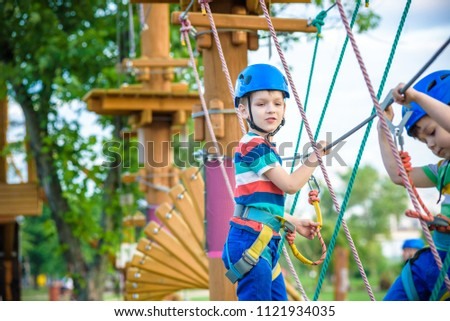 Young boy playing and having fun doing activities outdoors. Happiness and happy childhood concept. Boy swing on rope. #1121934035
