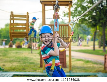 Young boy playing and having fun doing activities outdoors. Happiness and happy childhood concept. Boy swing on rope. #1121934038