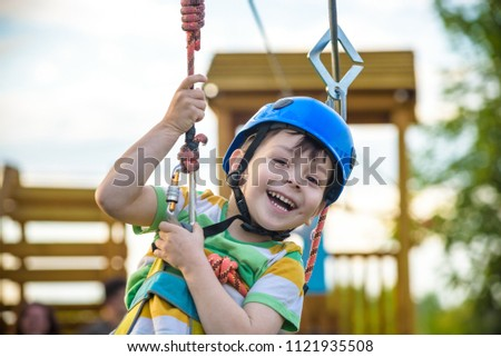 Young boy playing and having fun doing activities outdoors. Happiness and happy childhood concept. Boy swing on rope. #1121935508