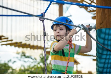 Young boy playing and having fun doing activities outdoors. Happiness and happy childhood concept. #1121935538