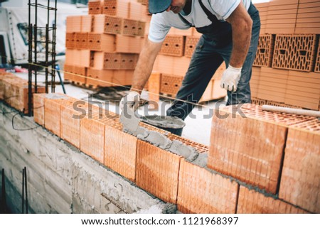 Bricklayer industrial worker installing brick masonry on exterior wall with trowel putty knife #1121968397