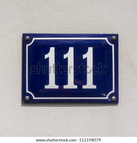 enameled house number one hundred and eleven. White lettering on a blue background