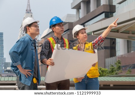 Asian male engineer, caucasian female engineer and technician operator with safety helmet and blueprint working at the construction site. Teamwork and engineering concept. #1121999933