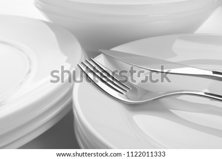 Many stacked plates with fork and knife, closeup #1122011333