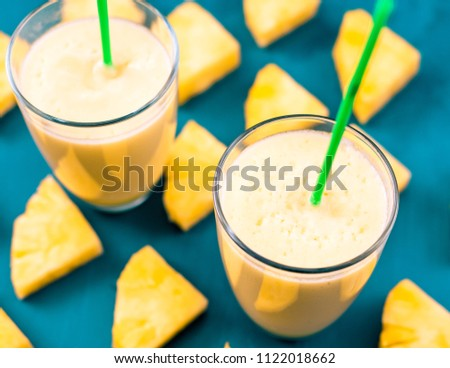 Pineapple smoothie with fresh pineapple on wooden blue table. #1122018662