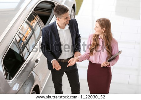 Young saleswoman working with client in car dealership #1122030152