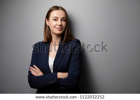Confidence and charisma. Young business woman in suit looking at camera. Grey background. #1122032252