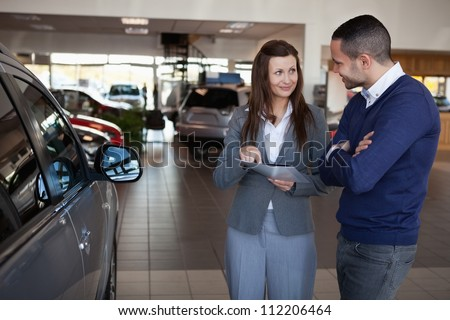 Woman explaining something to a man in a dealership #112206464