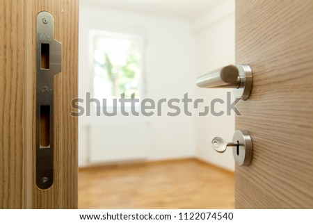 New apartment - House key in the door to modern living room #1122074540