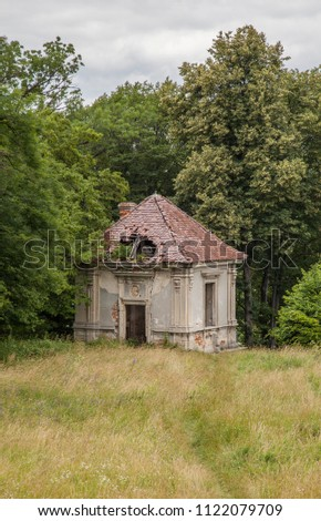 Very old historic building with wonderful architecture Old stones in the nature of the stone building is a wonderful design pastel grey color shades of green nature. #1122079709