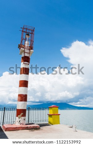 Red white lighthouse at lake with mountain background #1122153992
