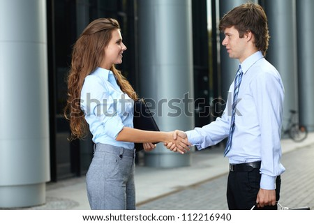 Handshake business smiling attractive young couple before the meeting, background #112216940