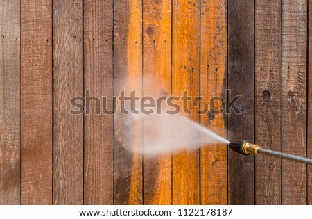 High pressure power washer spraying and cleaning wooden fence. Make old turn new. Dirty fence turned brand new again. Brown dirty grimy wood turned into golden oak again Royalty-Free Stock Photo #1122178187