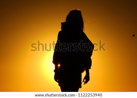 Beautiful silhouette on a warm sunset #1122253940