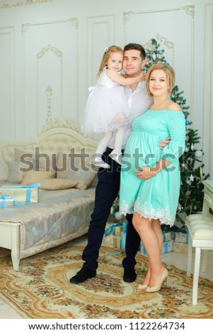 Pregnant european woman wearing blue dress standing with husband and little daughter near Christmas tree. Concept of winter holidays and family photo session.