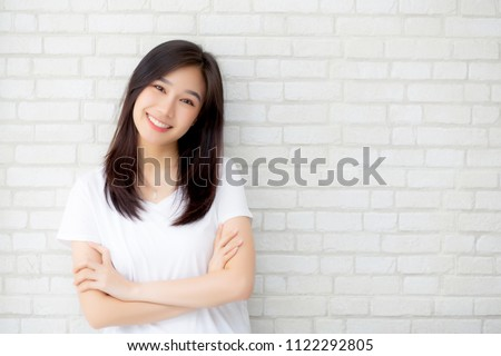 Portrait of beautiful young asian woman happiness standing on gray cement texture grunge wall brick background, businesswoman is a smiling on concrete, business people concept. #1122292805