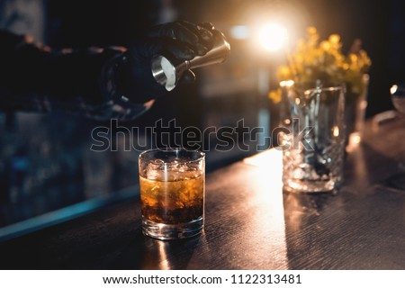 barman preparing luxury drink on the bar and with decoration; bartender making cocktail with icecream on backlighted background;  #1122313481