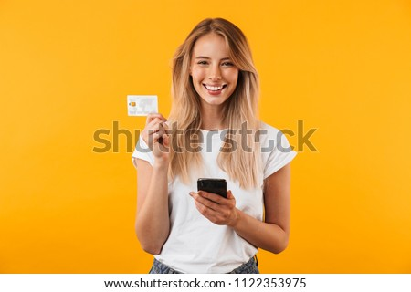 Portrait of a happy young blonde girl showing plastic credit card while holding mobile phone isolated over yellow background #1122353975