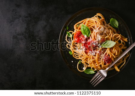 Tasty appetizing classic italian spaghetti pasta with tomato sauce, cheese parmesan and basil on plate on dark table. View from above, horizontal #1122375110