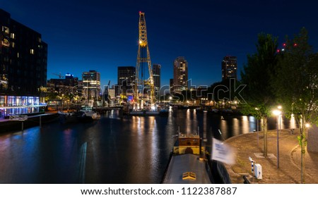Rotterdam, Netherlands - June 26, 2018: Rotterdam at the Leuvenhaven during nighttime with big crane on the water. #1122387887