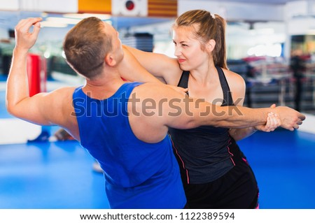 Positive cheerful  woman is training with man on the self-defense course in gym. Royalty-Free Stock Photo #1122389594