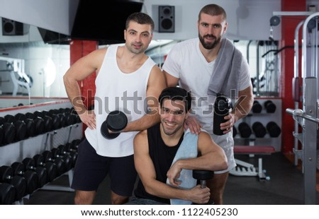 Portrait of three positive athletic male friends in modern gym #1122405230
