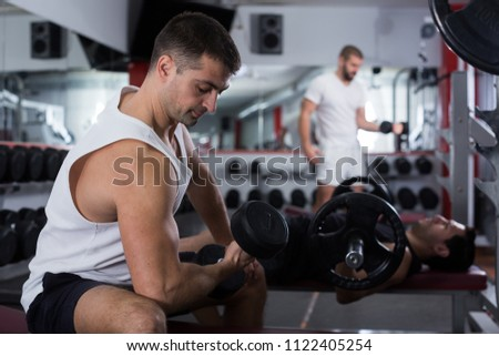 Muscular young man doing exercises with dumbbells at gym #1122405254