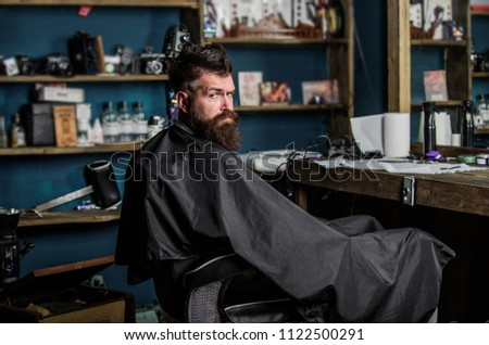Man with beard covered with black cape sits in hairdressers chair in front of mirror. Hipster with beard waits for barber and haircut. Man with beard client of hipster barbershop. Barbershop concept. #1122500291