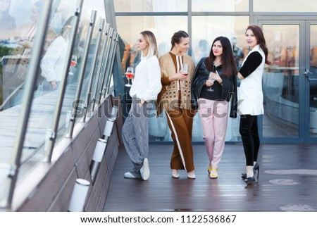 Four successful young female employees of large business companies celebrate a corporate party with a glass of wine in hands on an outdoor terrace #1122536867