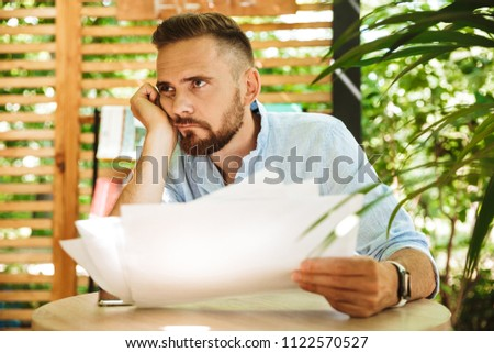 Image of young confused tired bearded man outdoors holding documents. #1122570527