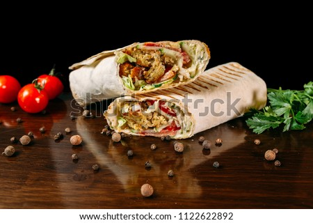 Shawarma sandwich gyro fresh roll of lavash (pita bread) chicken beef shawarma falafel RecipeTin Eatsfilled with grilled meat, mushrooms, cheese. Traditional Middle Eastern snack. On wooden background #1122622892