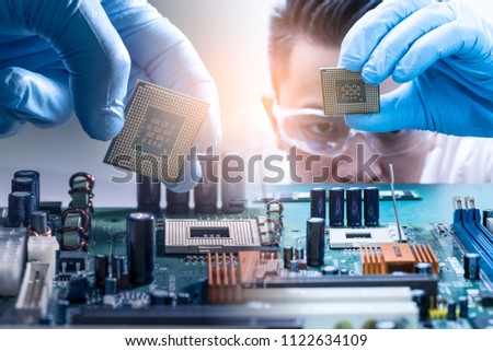 The asian technician is putting the CPU on the socket of the computer motherboard. the concept of computer hardware, repairing, upgrade and technology. #1122634109