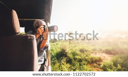Woman photographer takes a picture with professional camera from touristic vehicle on tropical safari #1122702572